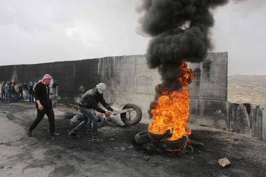 A Palestinian protester places a tyre on a burning pile during clashes with Israeli troops near Israels controversial barrier that separates the West Bank town of Abu Dis from Jerusalem November 17, 2014. REUTERS-Ammar Awad