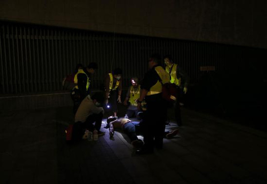 A pro-democracy protester is examined by rescue volunteers after being pepper sprayed by the police as he and others tried to break into the Legislative Council in Hong Kong early November 19, 2014, in response to an earlier clear up by bailiffs on part of the Occupy Central protest site. REUTERS-Tyrone Siu