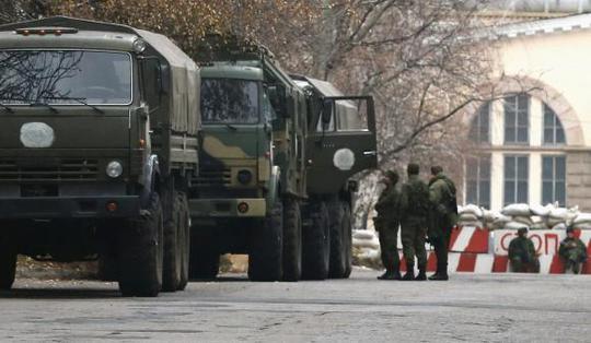 Armed people and military trucks are seen near a checkpoint outside a building on the territory controlled by the self-proclaimed Donetsk Peoples Republic in Donetsk, eastern Ukraine, November 12, 2014. REUTERS/Maxim Zmeyev