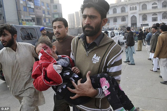 A Pakistani girl, who was injured in the attack, is rushed to a hospital in Peshawar
