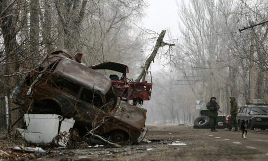 Pro-Russian separatists stand guard next to cars damaged during fighting between pro-Russian rebels and Ukrainian government forces near Donetsk Sergey Prokofiev International Airport, eastern Ukraine, December 16, 2014. REUTERS/Maxim Shemetov