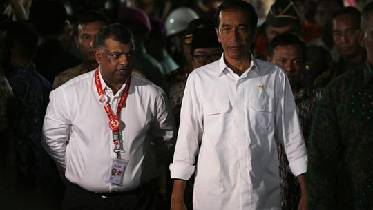 Indonesias President Joko Widodo (right) walking beside AirAsias CEO Tony Fernandes after meeting with family members of passengers onboard AirAsia flight QZ8501 in Juanda International Airport, Surabaya on Dec 30, 2014. -- PHOTO: REUTERS
