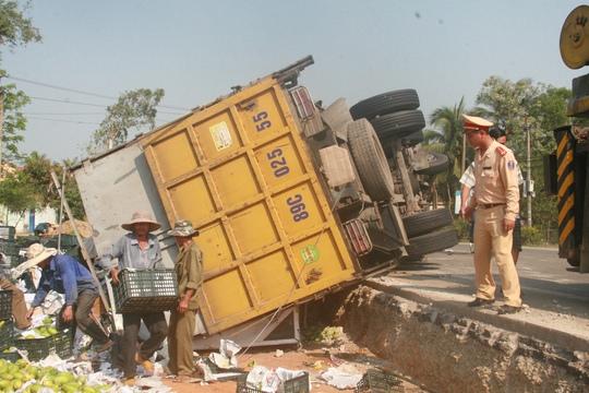 Chiếc xe tải chở trái cây bị lật nằm sóng soài trên đường