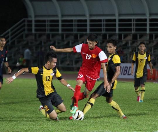 Văn Long đi bóng qua 2 hậu vệ Malaysia
