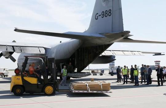 Quan tài chứa thi thể nạn nhân được đưa lên máy bay ở sân bay Kharkov để đến Hà Lan hôm 23-7. Ảnh: REUTERS