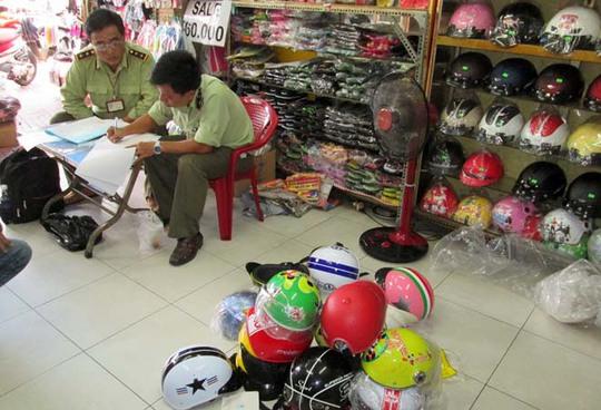Đội quản lý thị trường 5B lập biên bản một cửa hàng bán mũ bảo hiểm vi phạm