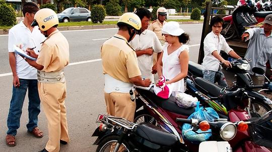 CSGT xử phạt những người đi xe máy không đội mũ bảo hiểm trên đường xuyên Á, Q.12, TP.HCM - Ảnh: N.C.T.