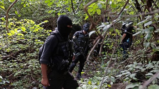 Cảnh sát Mexico đang bảo vệ khu mộ tập thể. Ảnh: Reuters