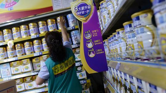 Một nhân viên đang kiểm tra hàng trong một siêu thị sữa bột ở Bắc Kinh