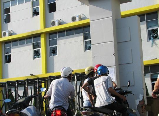 Công nhân Việt Nam Mỹ Thanh đang đọc thông báo. Phía trong là những cửa sổ công bị đập vỡ tan hoang