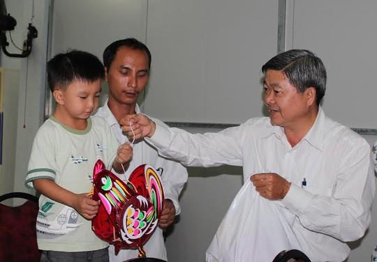 Ông Nguyễn Văn Dễ, Chủ tịch LĐLĐ quận Bình Tân, TP HCM, tặng lồng đèn cho con công nhân khó khăn ảnh: THANH NGA