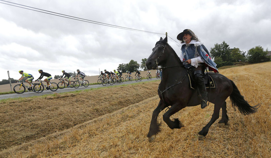 Một đàn ông cưỡi ngựa chạy theo đoàn đua ở chặng 19 của giải