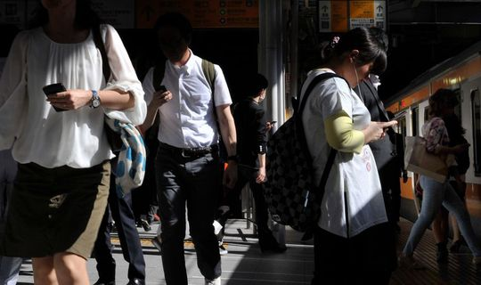 Người dân Tokyo dùng điện thoại tại nhà ga JR Shinjuku. Ảnh: Asahi