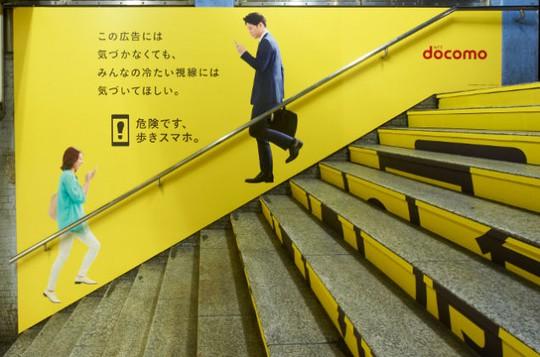Tấm biển cảnh báo người đi đường không nên dùng điện thoại tại cầu thang nhà ga JR Shinjuku ở Tokyo. Ảnh: kotaku.com