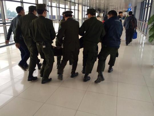 Lực lượng an ninh huy động gần chục người để khiêng hành khách gây rối ra ngoài khu vực nhà ga. Ảnh: otofun