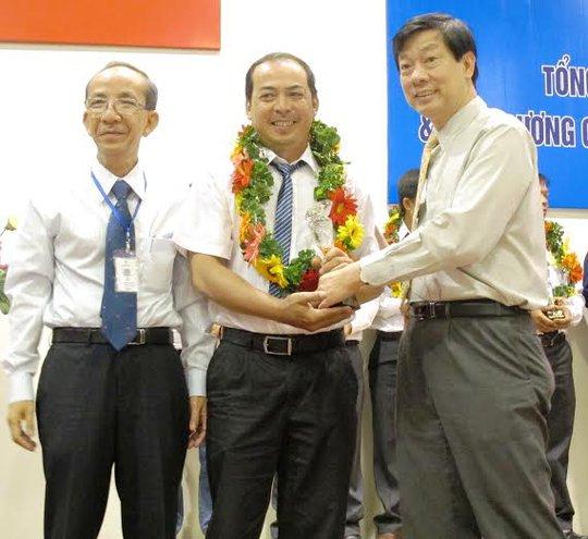 Công nhân của Tổng Công ty Điện lực TP HCM nhận biểu trưng khen thưởng của lãnh đạo tổng công ty ảnh: HỒNG NHUNG
