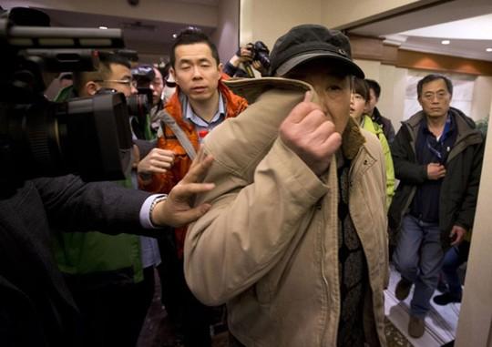 Một người đàn ông che mặt khi vào phòng họp báo tại Bắc Kinh (Nguồn: AFP)