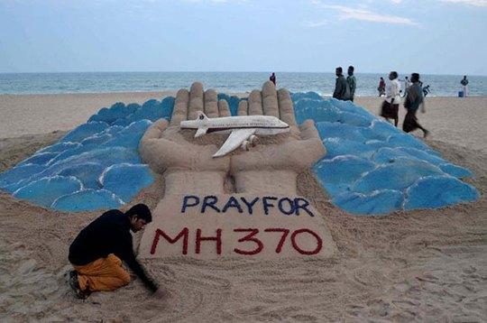 Nghệ sĩ điêu khắc cát Sudarshan Pattnaik bên tác phẩm cầu nguyện cho chuyến bay mất tích MH370 trên bãi biển ở Puri - Ấn Độ. Ảnh: Stringer