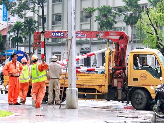 Công nhân tháo dỡ các biển báo trên các tuyến đường Lê Lợi, Nguyễn Huệ chiều ngày 22-7