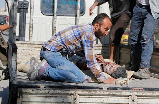 Ôm những thi thể người thân trong tay mà không kìm được nước mắt. Ảnh: Reuters