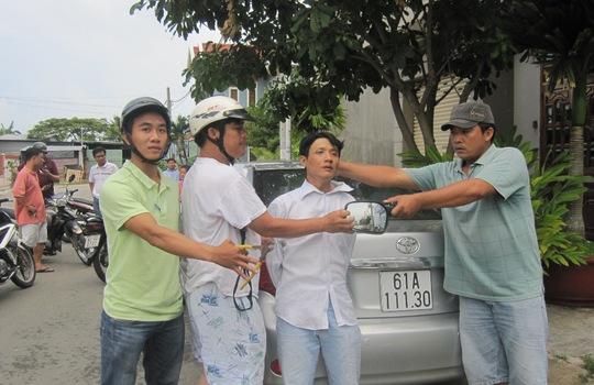 """Nguyễn Hữu Sang (đứng thứ 3 từ trái sang), cùng chiếc kính chiếu hậu của xe ôtô biển số 61A-111.30, bị """"hiệp sĩ"""" Nguyễn Thanh Hải cùng đồng đội bắt giữ."""