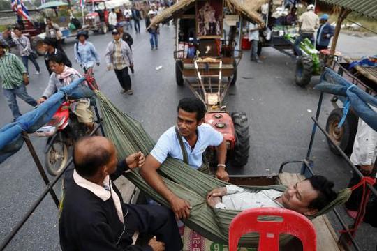 Nông dân Thái Lan nghỉ ngơi trên đường cao tốc ở Ayutthaya ngày 21-2. Ảnh: Reuters