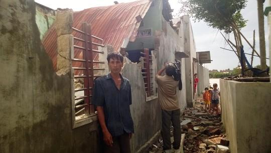 Người đàn ông này thẫn thờ trước ngôi nhà bị tốc mái, sập tường sau khi bão đi qua
