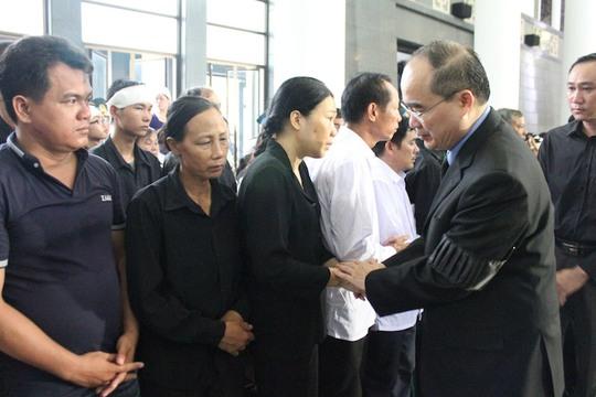 Chủ tịch UB Mặt trận tổ quốc Việt Nam Nguyễn Thiện Nhân nắm chặt tay động viên thân nhân cán bộ, chiến sỹ hy sinh