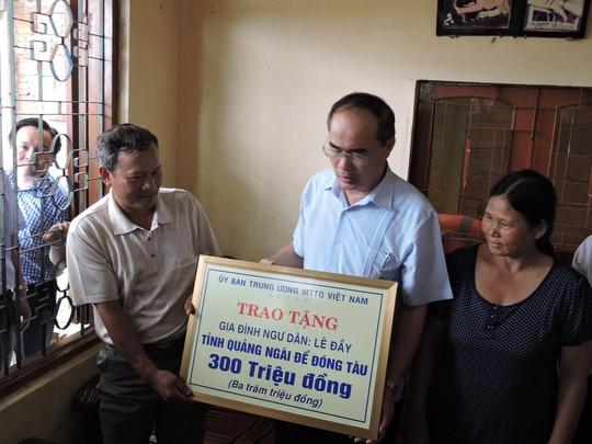 Ông Nguyễn Thiện Nhân, Chủ tịch UBTU7MTTQ Việt Nam (giữa), trao tiền hỗ trợ cho gia đình ngư dân Lê Đầy