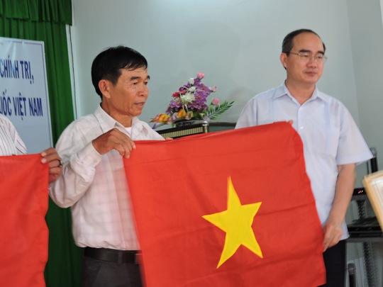 Ông Nguyễn Thiện Nhân, Chủ tịch UBTƯMTTQ Việt Nam (phải), trao cờ tổ quốc cho đại diện nghiệp đoàn nghề cá