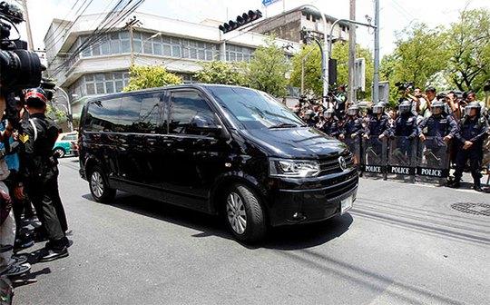 Bà Yingluck đến địa điểm trình diện ở khu vực Thewes, Bangkok trên một chiếc xe chống đạn Volkswagen màu đen có đội vệ sĩ đi kèm. Ảnh: Reuters