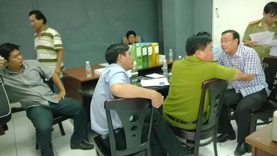 Ông Nguyễn Hữu Nghĩa, chủ nhà xưởng (bìa phải), đang trình bày sự việc với các cơ quan chức năng quận 12, TP HCM