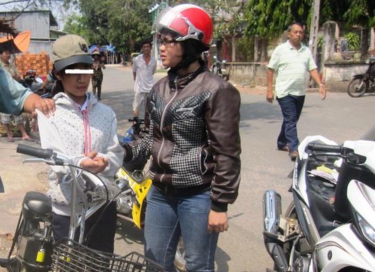 Trang (bìa trái) bị nữ hiệp sĩ Nguyễn Hồng Xuân Trường chặn lại cùng với chiếc xe đạp điện vừa trộm