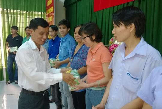 Ông Huỳnh Văn Tuấn, cCủ tịch LĐLĐ huyện Hóc Môn, T P HCM tặng quà cho các gia đình tiêu biểu