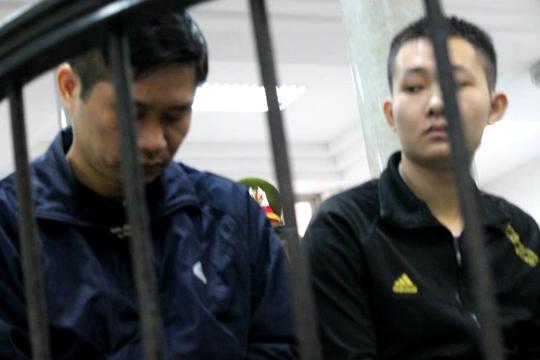 Nguyễn Mạnh Tường (trái) cúi mặt sau vàng móng ngựa cùng bảo vệ Đào Quang Khánh (phải)
