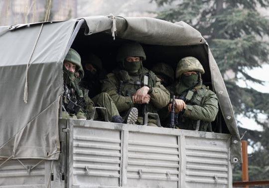 Binh lính ngồi trong xe quân sự Nga đậu bên ngoài một trạm gác biên giới của Urkaine nằm ở thị trấn Balaclava, Crimea hôm 1-3. Ảnh: Reuters