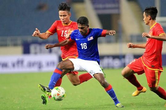 Hậu vệ Ngọc Hải (trái) vất vả trước cầu thủ Malaysia