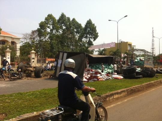 Hiện trường chiếc xe tải chở hàng lật ngang trên quốc lộ 14 (đoạn qua thi xã Đồng Xoài, tỉnh Bình Phước) vào sáng 27-3.