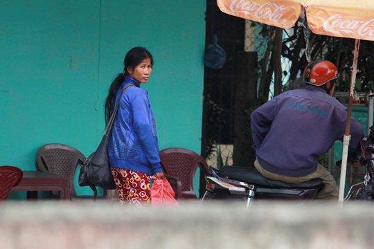 """Phía bên kia lộ cách đó không xa là một bà """"mẹ mìn"""" đang quan sát đám trẻ. Thoáng thấy ống kính của phóng viên, bà ta tò vẻ lo lắng và trốn đi"""