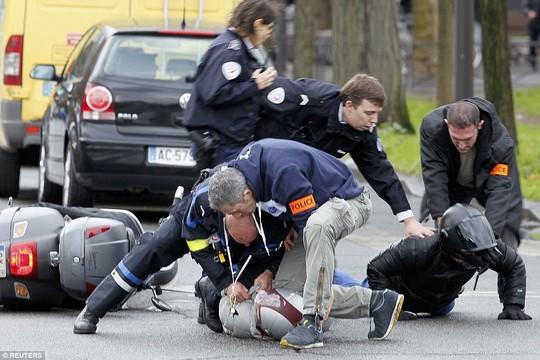 Cảnh sát ngăn chặn 2 người đi xe máy lại gần cửa tiệm. Ảnh: Reuters