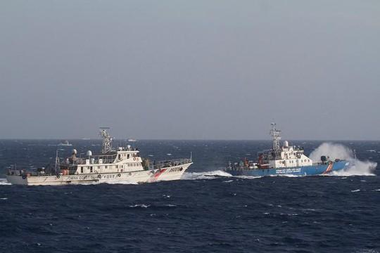 Tàu bảo vệ bờ biển Trung Quốc (trái) lượn lờ trên biển Đông. Ảnh: Reuters