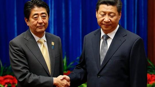 Chủ tịch Trung Quốc Tập Cận Bình (phải) và Thủ tướng Nhật Bản Shinzo Abe (trái) lãnh đạm bắt tay nhau tại Hội nghị APEC 2014. Ảnh: BBC