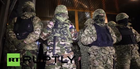 Lực lượng vũ trang chiếm đóng và dựng hàng rào xung quanh trụ sở Công ty dầu khí Ukrnafta tại thủ đô Kiev đêm 22-3. Ảnh: RT