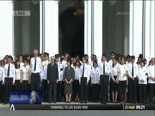 Tổng thống Singapore Tony Tan cùng 90 thành viên văn phòng thủ tướng, tổng thống đứng ngoài cung điện Istana tỏ lòng tôn kính. Ảnh: CNA