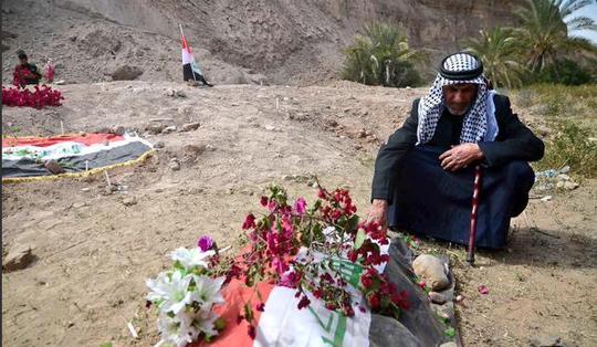 Cha một binh sĩ Iraq ngồi tại khu vực được cho là nơi con ông thiệt mạng tại TP Tikrit. Ảnh: Twitter