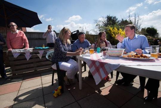 Thủ tướng Anh David Cameron (áo xanh bên phải) ăn tiệc ngoài trời hôm 6-4. Ảnh: PA