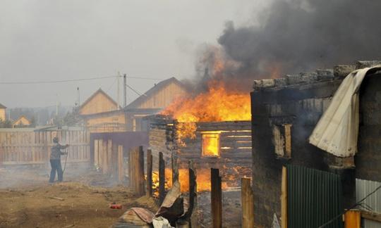 Một người đàn ông cố gắng dập lửa ở ngôi nhà của mình tại Smolenka, Siberia nhưng sau cùng nó cũng bị thiêu rụi. Ảnh: AP