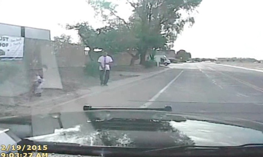 Chiếc xe cảnh sát đi theo ông Mario Valencia (áo thun trắng). Ảnh: AP