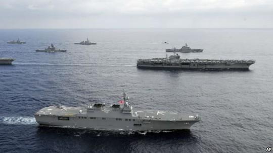Tàu sân bay Mỹ và tàu tuần tra của SDF trên biển Hoa Đông. Ảnh: AP