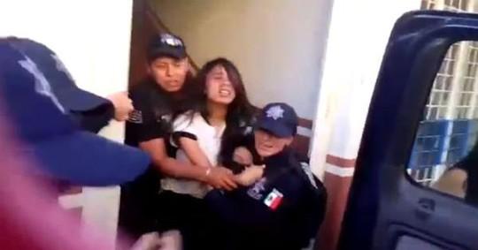 Ảnh cắt từ đoạn video quay cảnh bé gái 14 tuổi bị ép lên một chiếc xe của cảnh sát Mỹ. Ảnh: AP